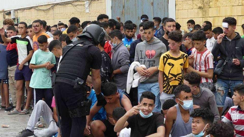 Un policía, junto a un grupo de menores marroquíes en el polígono de El Tarajal